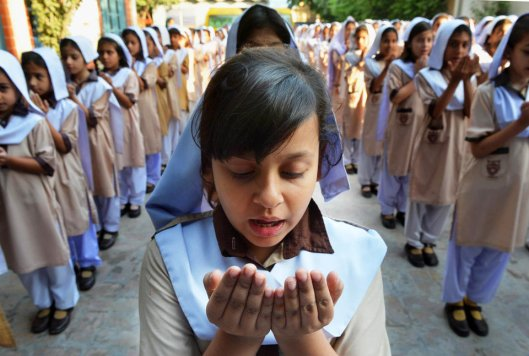 Pakistani school girls pray for the early recovery of child activist Malala Yousafzai, who was shot in the head in a Taliban assassination attempt, at their school in Peshawar on October 12, 2012. Pakistanis at mosques across the country prayed Friday for the recovery of a schoolgirl shot in the head by the Taliban as doctors said the next two days were critical. AFP PHOTO / A. MAJEED (Photo credit should read A. MAJEED/AFP/GettyImages)