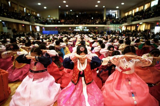 Students wearing traditional hanbok dresses bow as they attend a graduation and coming-of-age ceremony at the Dongmyeong girl's high school in Seoul on February 12, 2015. Around 500 students attended the ceremony, which signifies a child's passage into adulthood and aims to teach participants etiquette and the acceptance of responsibilities. Once a widespread tradition, coming-of-age ceremonies are increasingly rare with the event now usually observed in various less traditional ways. AFP PHOTO / Ed Jones (Photo credit should read ED JONES/AFP/Getty Images)